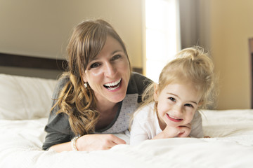 Mother and her daughter child girl taking good time on bed