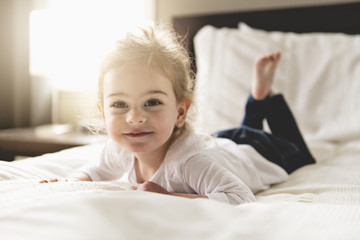 young daughter two years old relaxing in bed, positive feelings