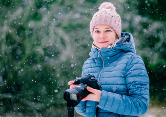 Portrait of beautiful young woman with camera on winter snow day