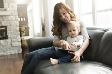 Beautiful mother and her cute little daughter are using a tablet at home