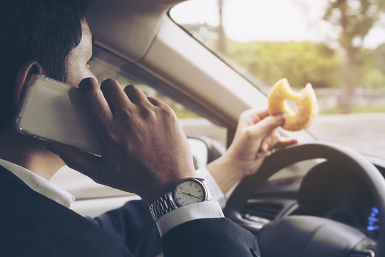 Man eating donuts while using mobile and driving car - multitasking unsafe driving concept