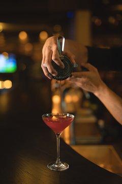 Waiter preparing cocktail drink at counter
