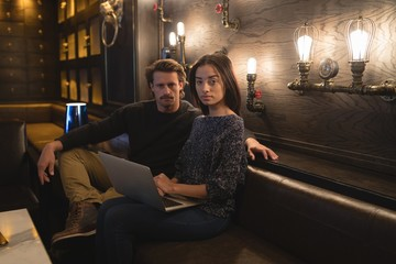 Couple using laptop in chocolate bar