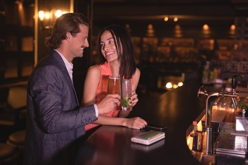 Couple toasting glasses of drinks at counter