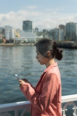 Asian woman using her phone in the ferry