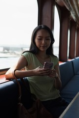 Asian woman using her mobile phone in the ferry