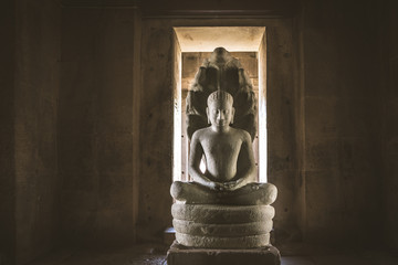 stone buddha in a khmer imperium ruins in thailand. isan.