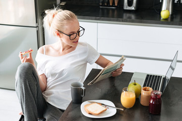 Serious focused lady reading newspaper while have breakfast
