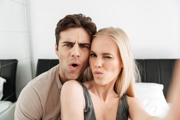 Funny attractive lovers making selfie and grimacing in the morning