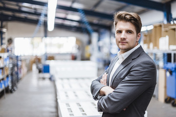Young manager standing in shop floor, portrait