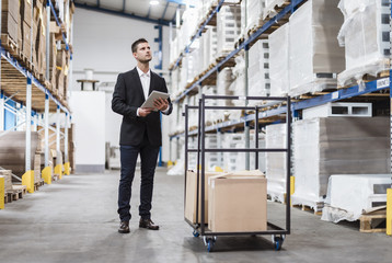 Businessman in warehouse loading cardboard boxes on transport cart
