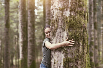 Smiling woman hugging a tree