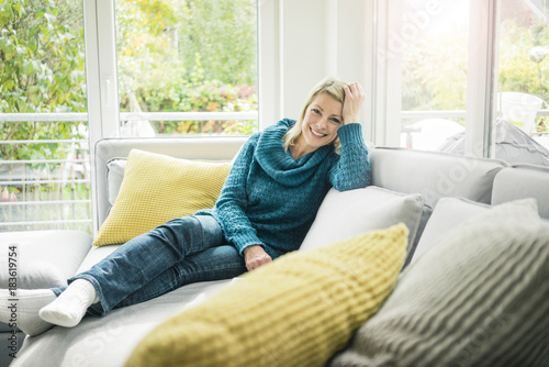 Portrait Of Hy Woman Relaxing On Couch