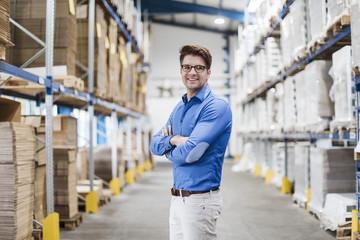 Businessman standing in warehouse, portrait