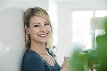 Portrait of smiling blond woman at home