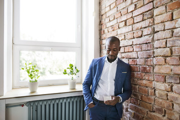 Businessman using cell phone at brick wall by the window