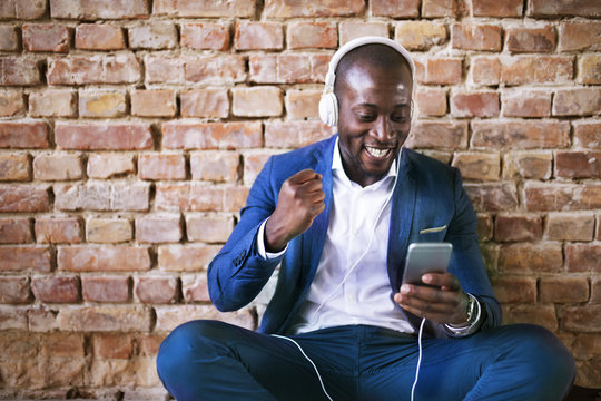 Happy businessman with headphones and smartphone cheering