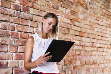 Businesswoman holding clipboard at brick wall in office