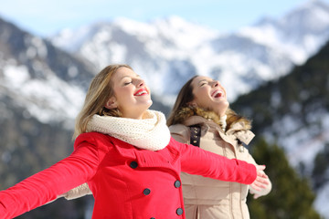 Two friends breathing fresh air in winter in the mountain