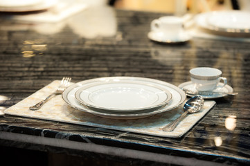 Ceramic plates ,fork and spoon,tea cup and mat  on the stone table.