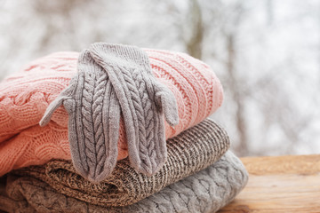 Stack of knitted clothes on wooden tableon winter nature background.