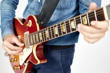 Chitarrista con chitarra elettrica rossa e giacca di jeans