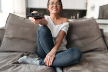 Happy young woman sitting on sofa at home watch TV.