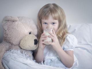 Little girl drinks milk before bedtime