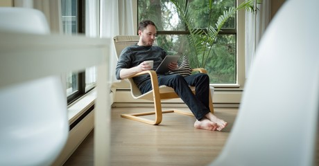 Man using digital tablet while having coffee in living room