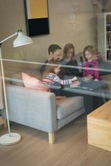 Family using digital tablet in living room