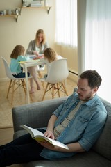 Father reading a book while mother helping her children in