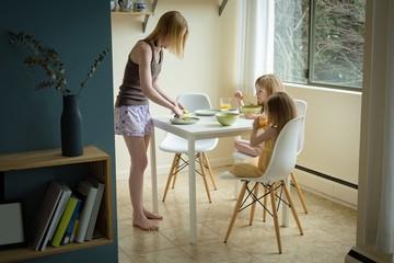 Mother serving breakfast to her children