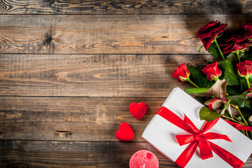 Holiday  background, Valentine's day. Bouquet of red roses, tie with a red ribbon, with wrapped gift box. On wooden table, copy space top view
