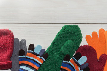 Winter children's mittens lie on a wooden background
