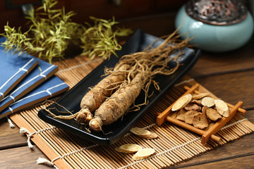 .ginseng in black plate on wooden table Wall mural