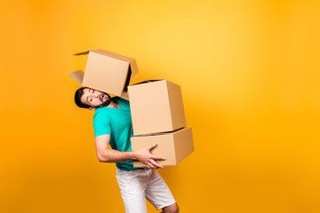 It's moving day! Busy funny guy in casual clothes is carrying big boxes in his hands and trying to keep one using his head, isolated on yellow background