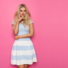 Beautiful Blond Woman In Blue And White Dress Is Looking Away