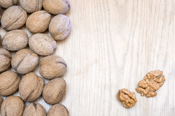 Isolated walnut in shell and peeled walnut kernel on a wooden table. Healthy food. Place for text.