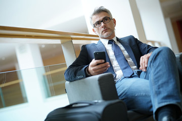 Businessman in airport waiting area connected with smartphone