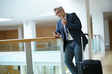 Businessman with suitcase at airport departure hall