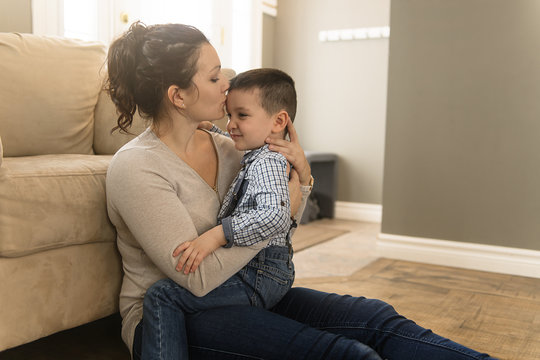 mother with boy sitting on couch at home