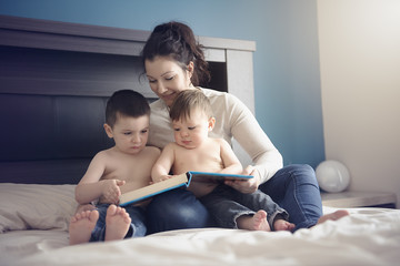mother reading a book with her two childs boys in the bedroom
