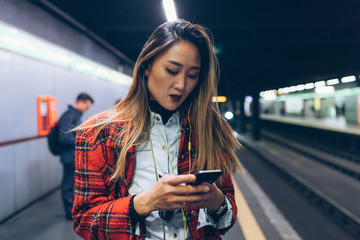 young woman underground using smart phone - technology, commuting, traveller concept