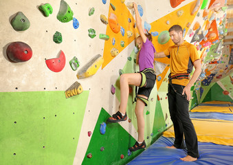 Little girl with trainer in climbing gym