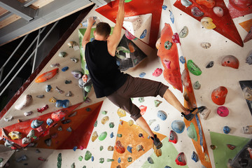 Young man exercising in climbing gym