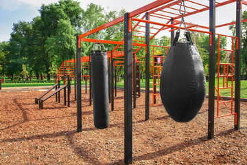 Punching bags for boxing on athletic field in park