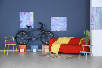 Modern room interior with bicycle and red sofa