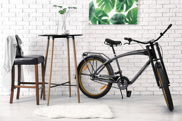 Modern room interior with small table and bicycle