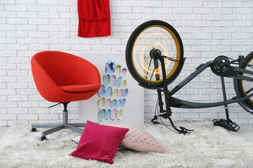 Room interior with red armchair and bicycle