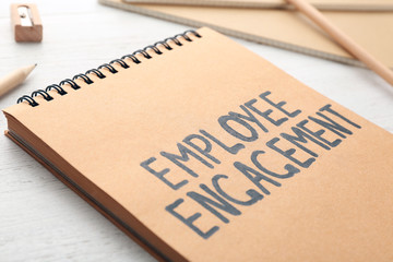 Notepad with text EMPLOYEE ENGAGEMENT on table